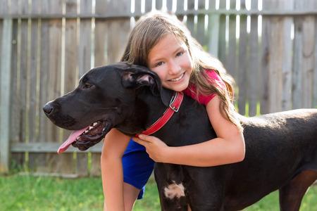 great dane and kid girl hug playing together at backyard outdoor photo