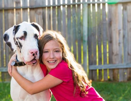 dane: great dane and kid girl hug playing together at backyard outdoor Stock Photo