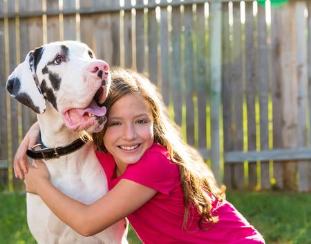 big dog: great dane and kid girl hug playing together at backyard outdoor Stock Photo