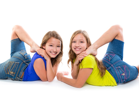 contortionist: twin kid sisters symmetrical flexible playing happy on white background Stock Photo