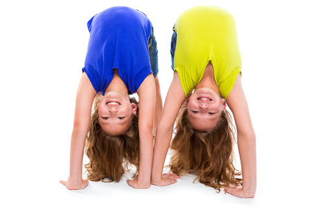 young girl smiling: twin kid sisters playing as flexible contortionist happy on white background