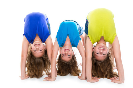 contortionist: twin kid sisters girls friends playing as flexible contortionist happy on white background