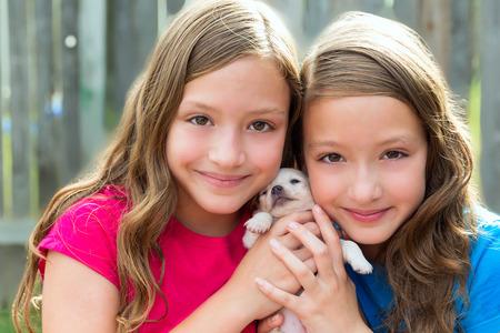 niñas gemelas: Hermanas gemelas y cachorro de perro mascota chihuahua que juegan juntos con el perrito