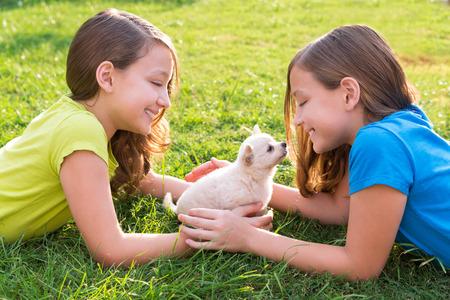 soeur jumelle: jumeau filles soeur kid et chiot heureux de jouer avec des animaux se trouvant dans la cour pelouse