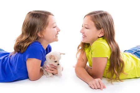 soeur jumelle: heureux jumeaux filles soeur kid et jeu chiot couch� sur fond blanc