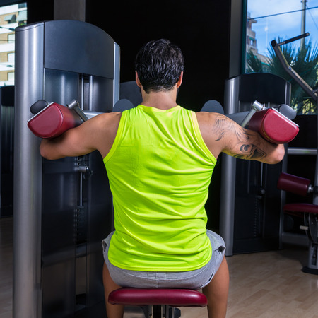 deltoids: Deltoids fly machine man for shoulders workout at gym