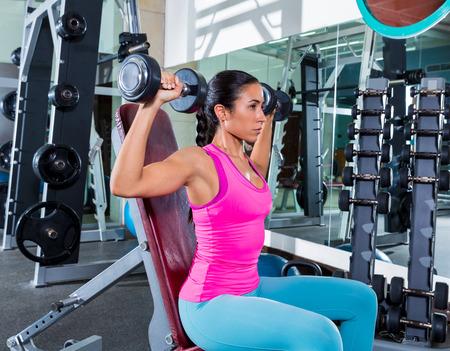 dumbbell: girl at gym seated dumbbell shoulder press workout exercise