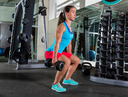 squat: dumbbell squat woman workout exercise at gym