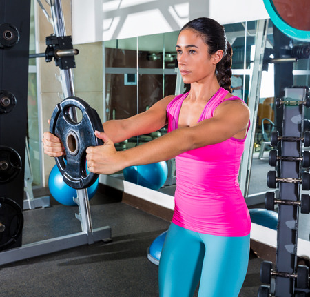 front raise: front plate raise brunette girl workout at gym exercise
