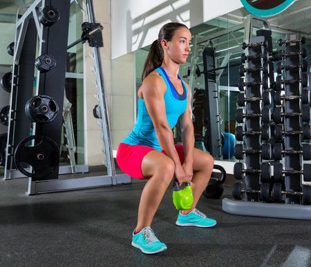 pesas: cubilete ejercicio de la mujer del entrenamiento de pesas rusas sentadillas en el gimnasio