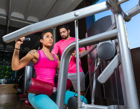 dorsal: Lat Lateral dorsal pulldown machine upper back woman with personal trainer man