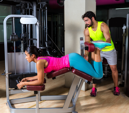 hamstring: Lying hamstring curl machine girl with personal trainer man