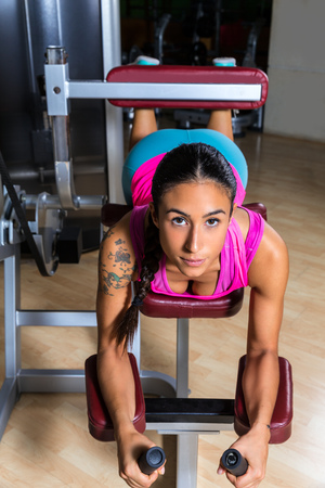 hamstring: Lying hamstring curl machine girl brunette woman Stock Photo
