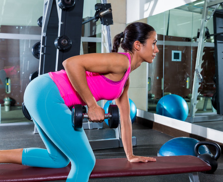 dumbells: girl one arm dumbbell bent over row on bench workout exercise at gym