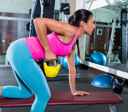 bent over: girl one arm kettlebell bent over row on bench workout exercise at gym