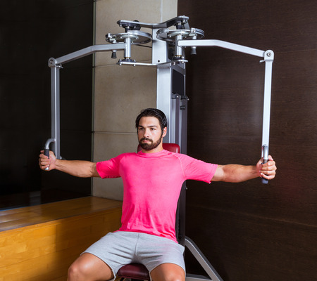 weight machine: pec-deck fly flies pec deck chest workout man exercise at gym Stock Photo