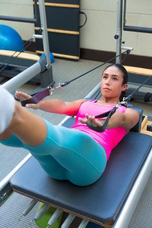 Pilates Reformer Workout-Übungen Frau Brunette auf Fitnessstudio Innen