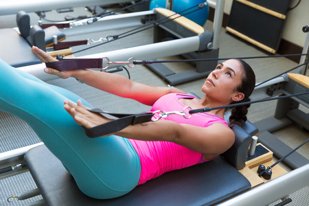 equipment: Pilates reformer workout exercises woman brunette at gym indoor