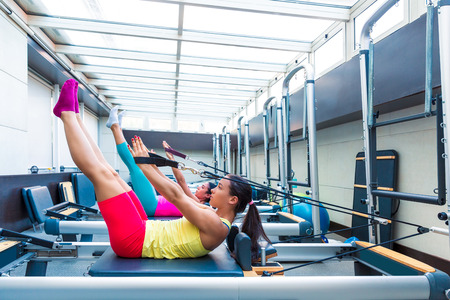 reformer: Pilates reformer workout exercises women at gym indoor Stock Photo