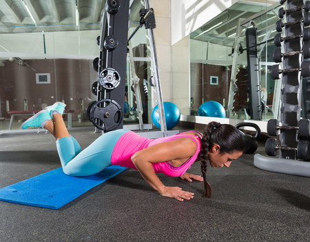knees up: brunette woman at gym knees push up push-up workout exercise