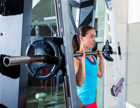 brunette girl in multipower barbell shoulder press Smith machine at gym photo