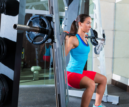 girl squatting: girl squats in multipower squatting smith machine barbell at gym smith Stock Photo