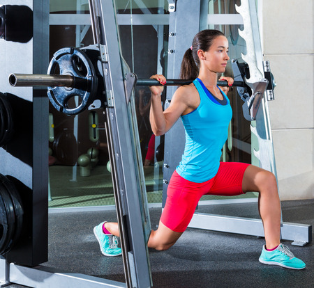 girl squats in multipower squatting smith machine barbell at gym smith Stock Photo