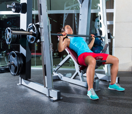 incline: Barbell Incline Bench Press woman in multipower Smith machine workout at gym Stock Photo