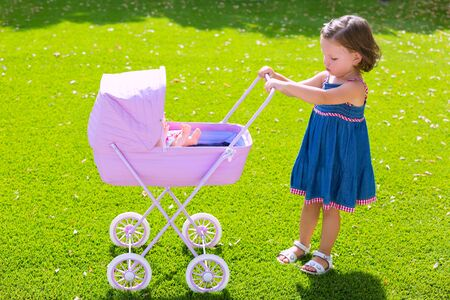 Toddler kid girl playing with baby cart in green turf grass garden photo