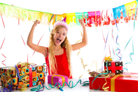 Party blond kid girl happy with many presents hands up excited photo