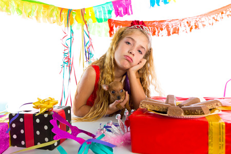 long hair chihuahua: Bored gesture blond kid girl in party with chocolates and puppy chihuahua dog