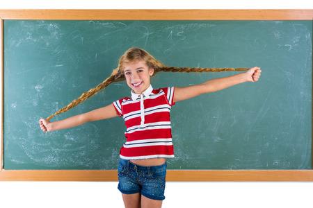 rubia ojos azules: Trenzado chica estudiante rubia jugando en pizarra verde con trenzas en el aula de la escuela