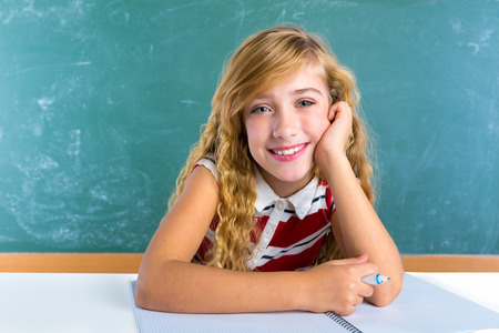 Happy student expression schoolgirl in classroom desk at school green chalk board photo