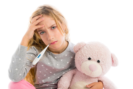 grumpy: blond girl with thermometer and flu cold in pyjama  grumpy face with teddy bear