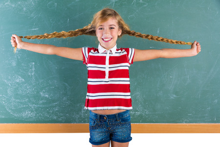 young schoolgirl: Braided student blond girl playing in green chalkboard with braids at school classroom
