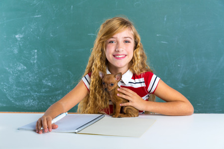 Blond student girl with puppy dog at class green chalk board sitting in desk photo
