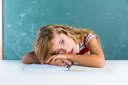 Boring sad expression student schoolgirl on classroom desk at school green chalk board photo