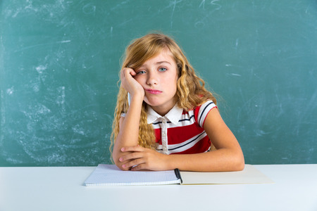 Boring sad expression student schoolgirl on classroom desk at school green chalk board Stock Photo