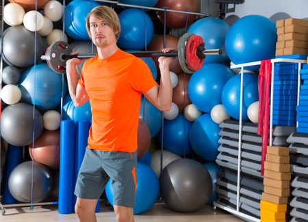 squats: barbell squats blond man at gym exercise workout Stock Photo