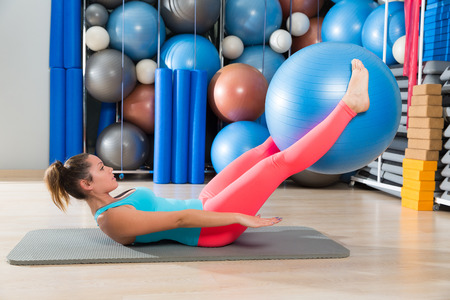 abs: Ab exercise woman swiss ball leg lifts Pilates workout abs at gym Stock Photo