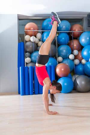 handstand: handstand woman workout at gym with swiss balls background