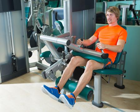 hombre sentado: Gimnasio pierna sentado máquina de curl ejercicio rubio hombre en cubierta