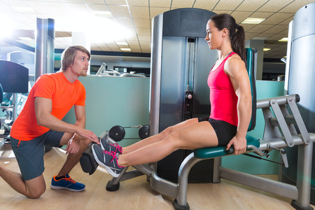 calf: Calf extension woman at gym exercise machine workout and personal trainer woman Stock Photo