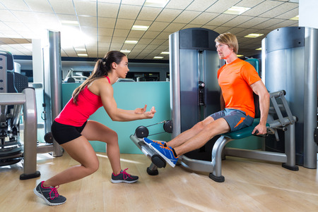 Calf extension man at gym exercise machine workout and personal trainer woman