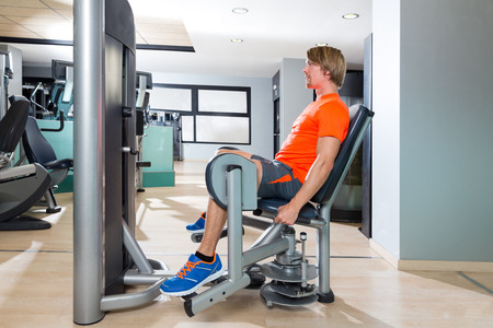 abductor: Hip abduction blond man exercise at gym indoor opening legs workout Stock Photo