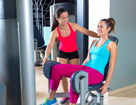 abductor: Hip abduction women exercise at gym indoor workout and personal trainer smiling Stock Photo