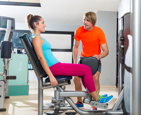 abduction: Hip abduction woman exercise at gym indoor closing legs and personal trainer blond man