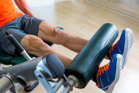 ジム屋内トレーニングで脚延長運動男