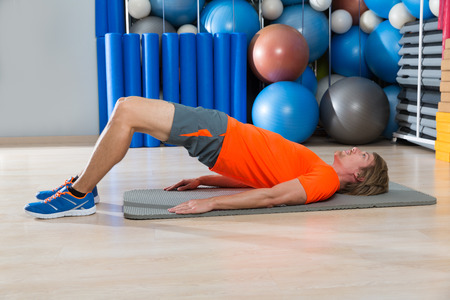 hip lift with blond man at gym workout with swiss ball background
