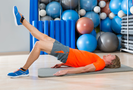 legs: hip lift with leg extension blond man at gym workout with swiss ball background
